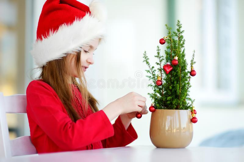 Adorable little girl wearing Santa hat decorating small Christmas tree in a pot on Christmas morning royalty free stock image