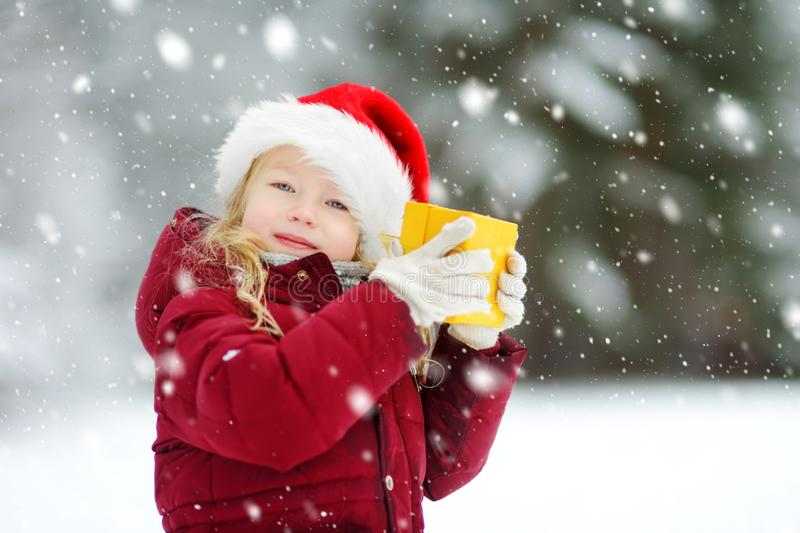 Adorable little girl wearing Santa hat holding Christmas gift on beautiful winter day stock photo