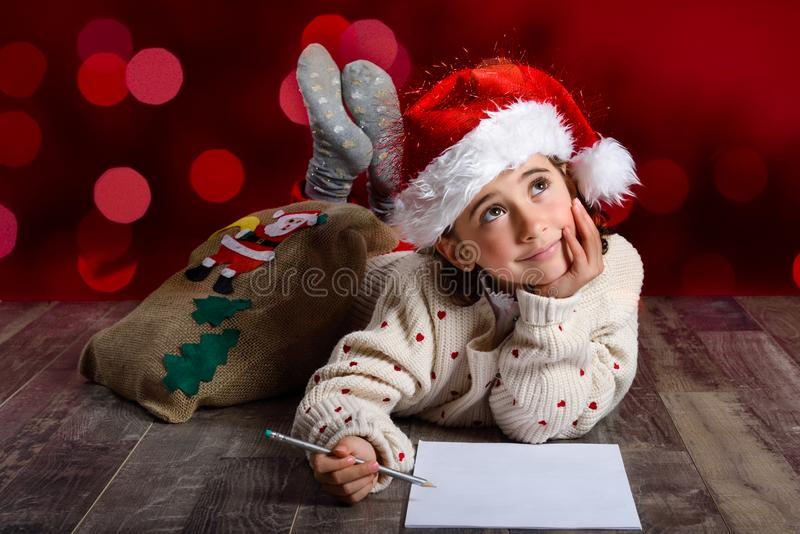 Adorable little girl wearing santa hat writing Santa letter royalty free stock images