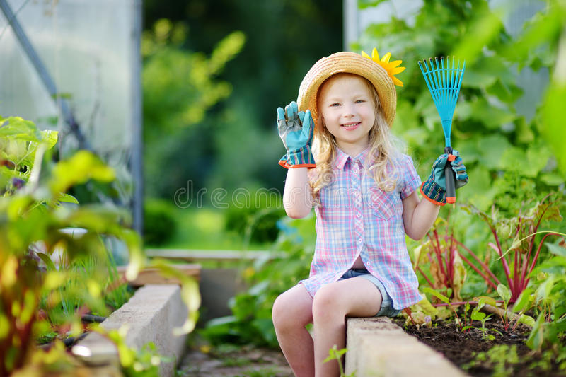 Adorable little girl wearing straw hat and childrens garden gloves playing with her toy garden tools in a greenhouse stock image