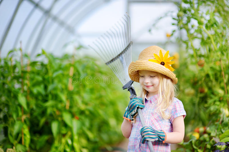Adorable little girl wearing straw hat and childrens garden gloves playing with her toy garden tools in a greenhouse. On sunny summer day royalty free stock photography
