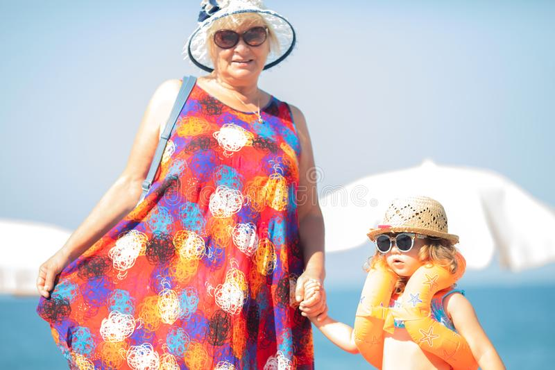 Adorable little girl wearing sunglasses, inflatable over-sleeves floats and inflatable donut float ring standing at the beach with. Her grandmotherSafety in the royalty free stock image