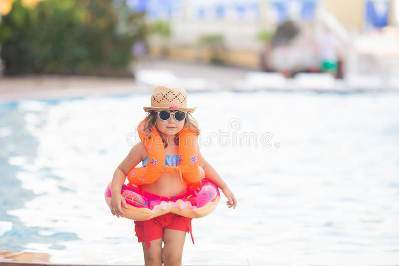 Adorable little girl wearing sunglasses, inflatable over-sleeves floats and inflatable donut float ring, swimming pool at the. Background. Safety in the water royalty free stock photo