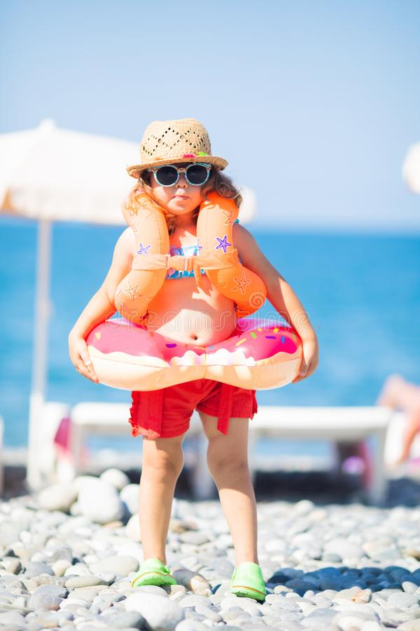 Adorable little girl wearing sunglasses, inflatable over-sleeves floats and inflatable donut float ring, sea coast at the. Adorable little girl wearing stock photos