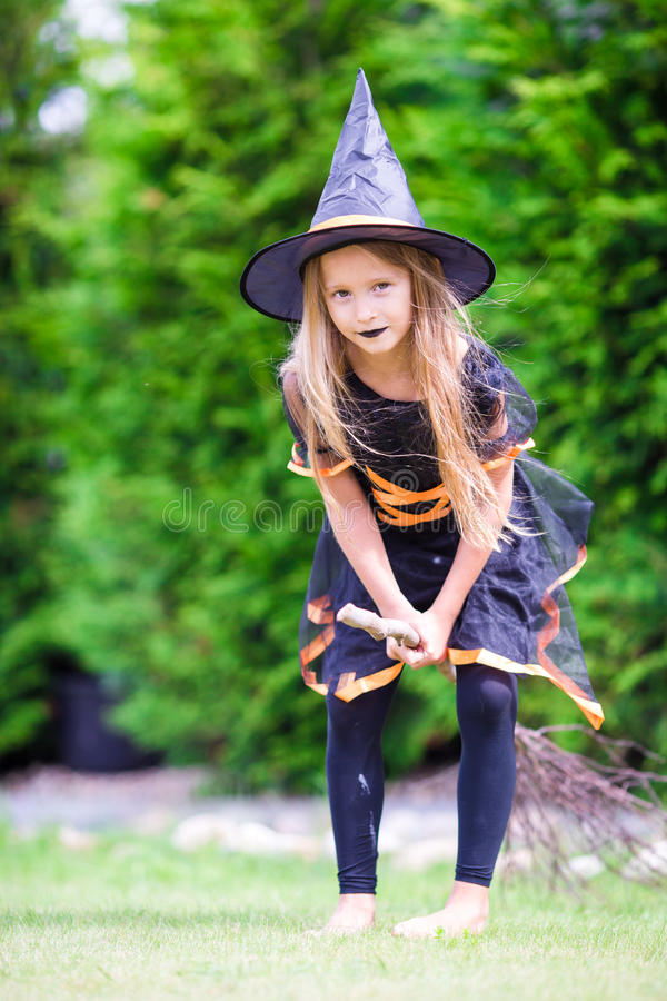 Adorable little girl wearing witch costume with stock photos