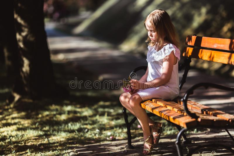 Adorable little girl in white dress in blooming pink garden on beautiful spring day royalty free stock photos