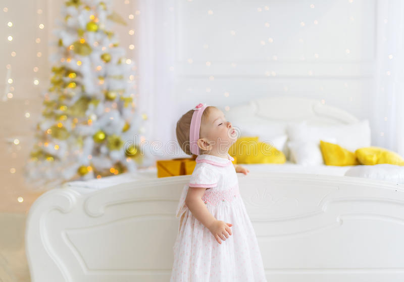 Adorable little girl in a white dress stand on a floor near christmas tree and makes a wish. stock photos