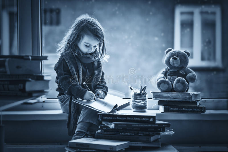 Adorable little girl, writing letter to Santa, sitting on a wind. Ow, books and teddy bear around stock photos