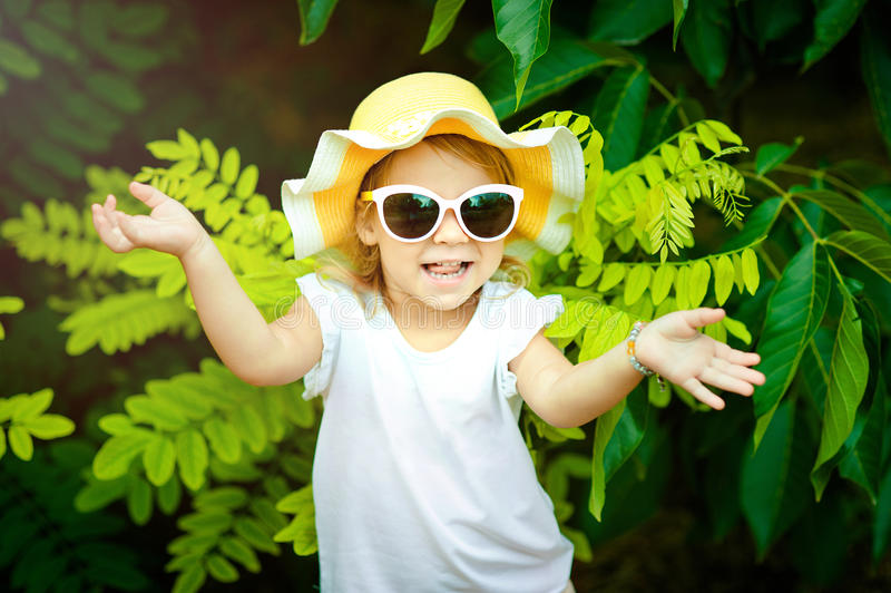 Adorable little girl In a yellow hat and pink sunglasses laughing in a meadow - happy girl stock photo