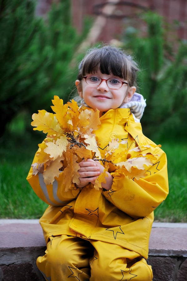 Adorable little girl in yellow raincoat royalty free stock photography