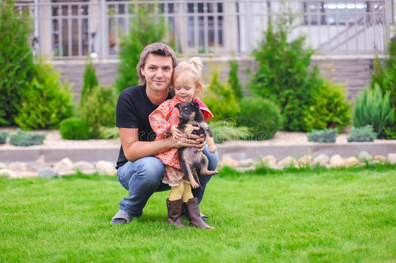 Adorable little girl and young father with puppy outdoors. Adorable little girl and her father with puppy outdoors royalty free stock photography