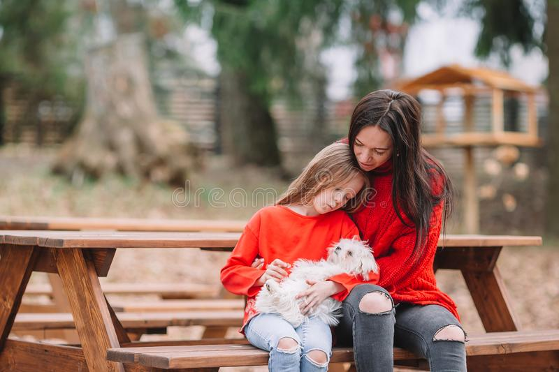 Adorable little girl and young mother with puppy outdoor. Adorable little kid and young mother with puppy outdoor royalty free stock photography