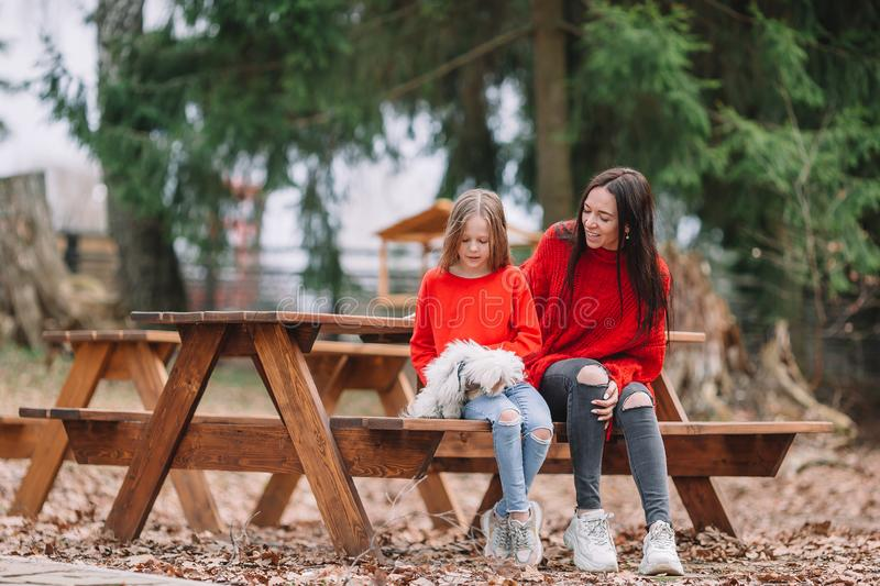 Adorable little girl and young mother with puppy outdoor. Adorable little kid and young mother with puppy outdoor stock photography