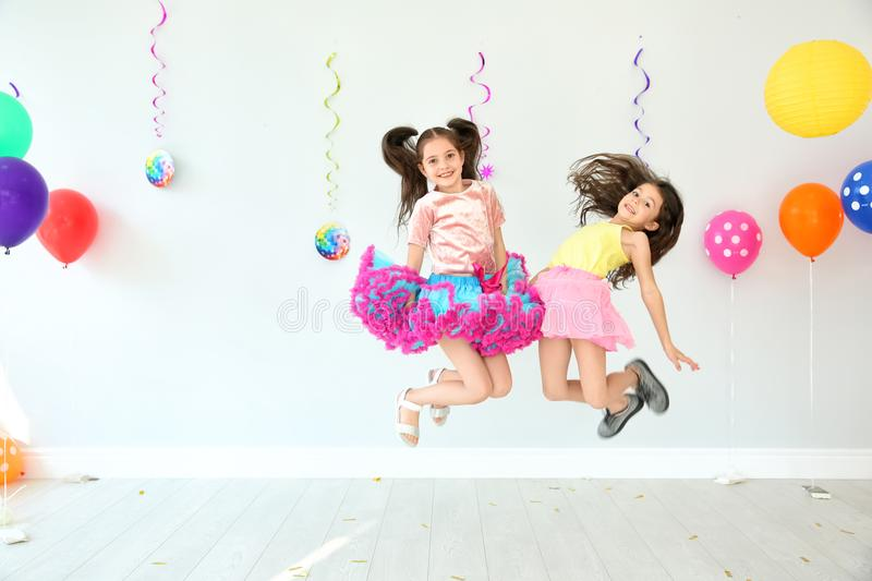Adorable little girls at birthday party indoors. Adorable little girls jumping at birthday party indoors royalty free stock photo