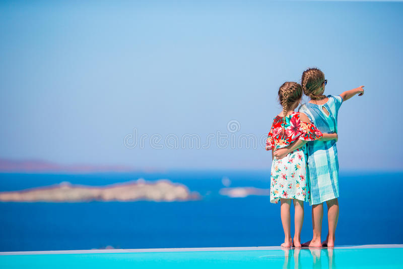 Adorable little girls on the edge of outdoor swimming pool with amazing view of old Mykonos town, Europe. Adorable little girls playing in outdoor swimming pool royalty free stock images