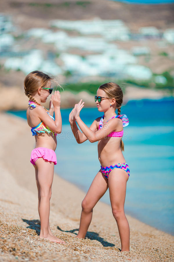 Adorable little girls having fun during beach vacation royalty free stock images
