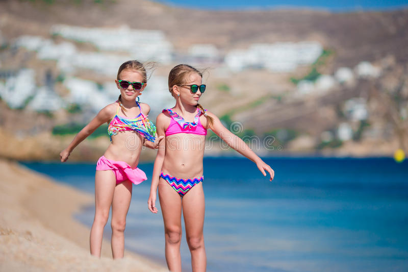 Adorable little girls having fun during beach vacation. Two kids together on greek vacation royalty free stock images