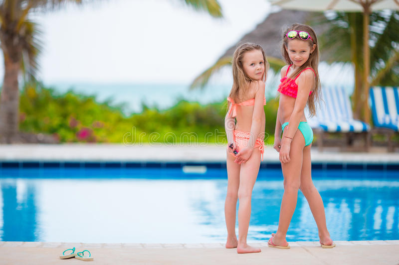 Adorable little girls having fun in outdoor swimming pool on summer vacation. Adorable little girls playing in outdoor swimming pool stock image
