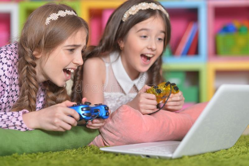 Portrait of adorable little girls playing computer game stock photography