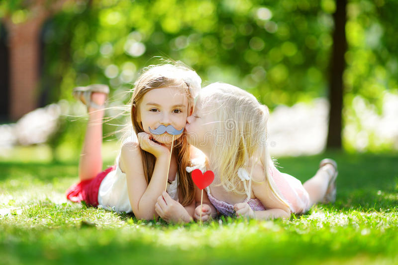 Adorable little girls playing with paper moustaches on a stick and other accessories royalty free stock photos