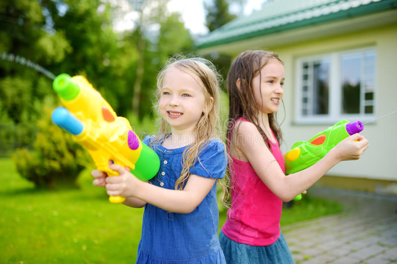 adorable little girls playing with water guns on hot summer day cute children having fun with. Black Bedroom Furniture Sets. Home Design Ideas