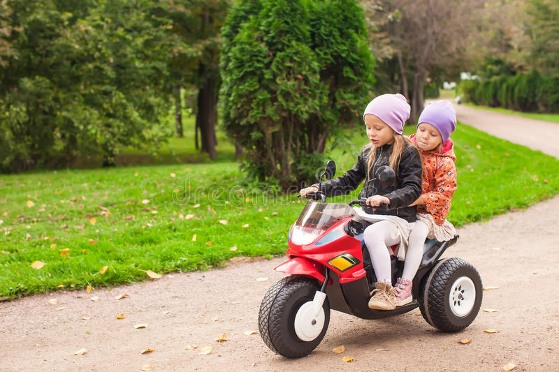 Adorable Little Girls Riding On Kid S Motobike In Royalty Free Stock Images