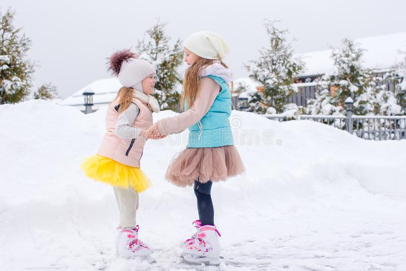 Adorable girls skating on ice rink outdoors in winter snow day. Adorable little girls skating on ice rink outdoors in winter snow day royalty free stock photography