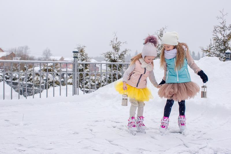 Adorable girls skating on ice rink outdoors in winter snow day. Adorable little girls skating on ice rink outdoors in winter snow day stock photography