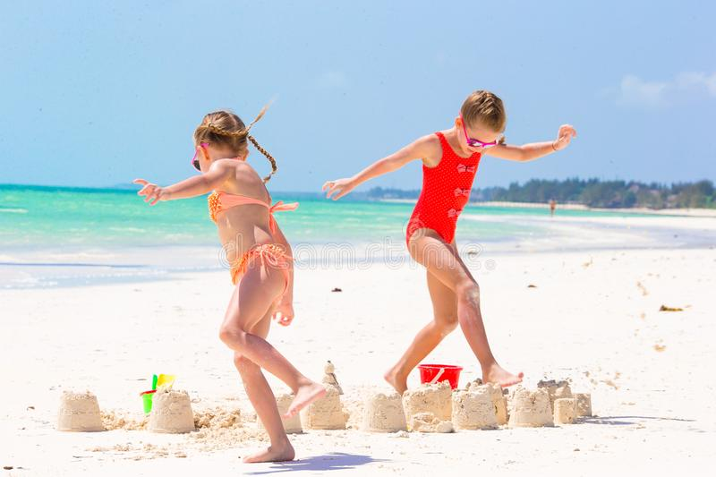 Adorable little girls during summer vacation. Kids playing with beach toys on the white beach. Adorable little girls during summer vacation on the beach stock images
