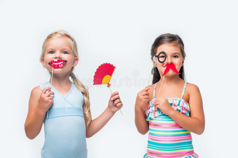 Adorable little girls in swimsuits holding party sticks and looking at camera. Isolated on white stock image