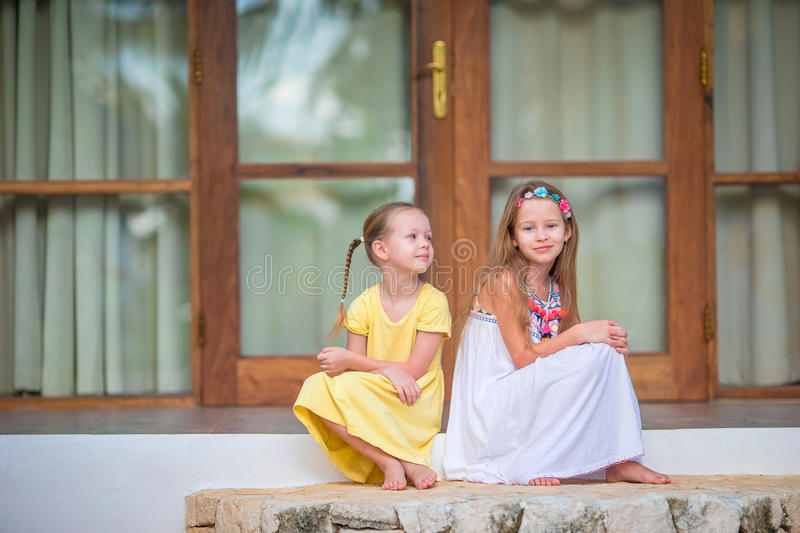 Adorable little girls on terrace during summer vacation stock image