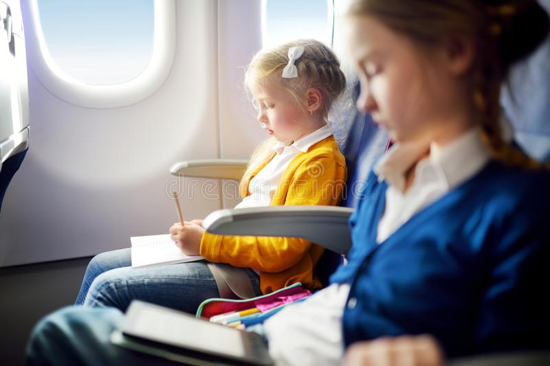 Adorable little girls traveling by an airplane. Child sitting by aircraft window and drawing a picture with colorful pencils. royalty free stock images