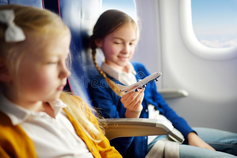 Adorable little girls traveling by an airplane. Children sitting by aircraft window and playing with toy plane. Traveling with kid stock images