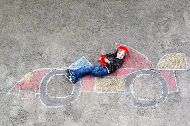 Adorable little kid boy drawing with colorful chalks race car picture on asphalt. Cute toddler and preschool child playing racing driver. Creative leisure with royalty free stock photo