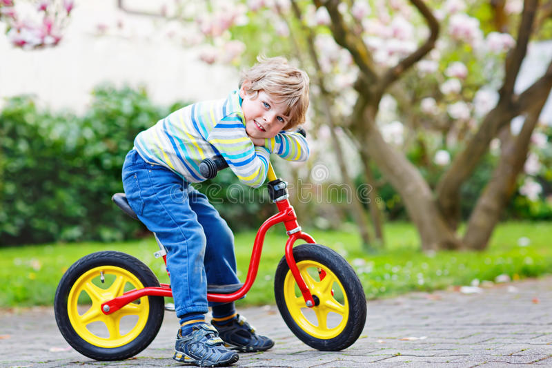 Adorable little kid boy driving his first bike or laufrad. Adorable little kid boy driving and running on bike or laufrad in park or garden on warm spring day royalty free stock images