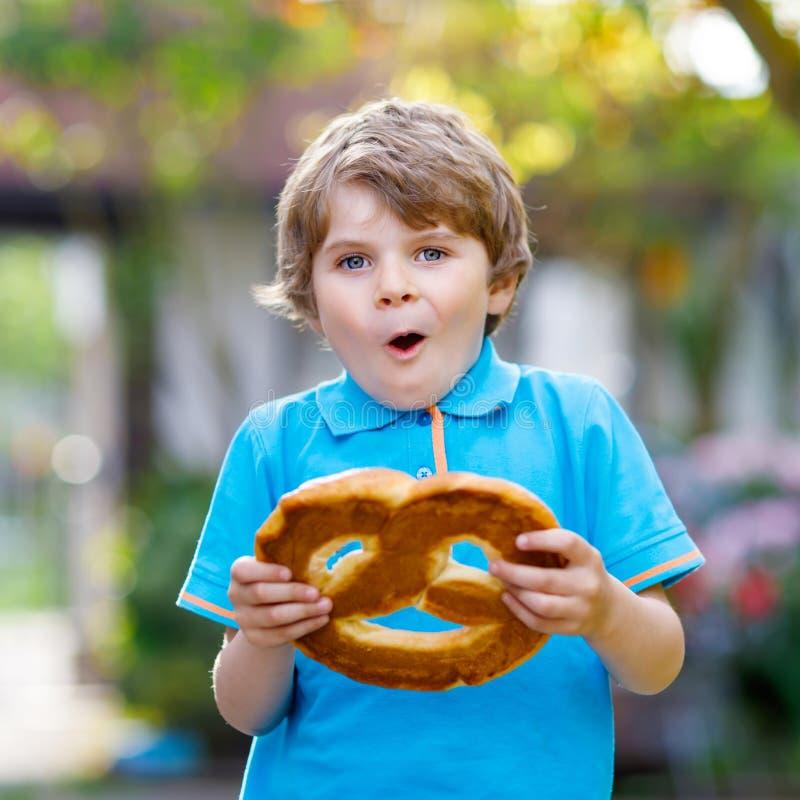 Adorable little kid boy eating huge big bavarian german pretzel. Happy blond child enjoying tasteful tratditional bread royalty free stock photography