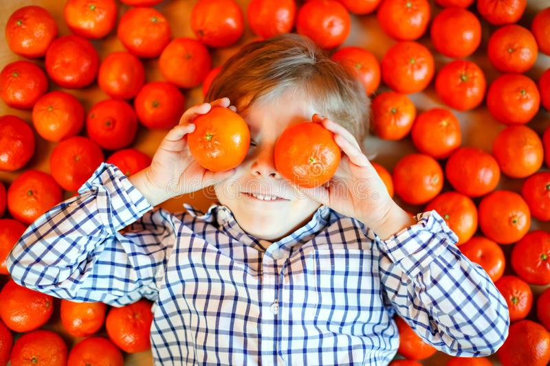 Adorable little kid boy with mandarin oranges background. Happy smiling child having fun with lot of fruits. Healthy stock photography