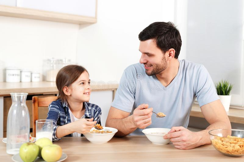 Adorable little kid and her father eat flakes together, have pleasant conversation with each other, sit at kitchen table stock photography