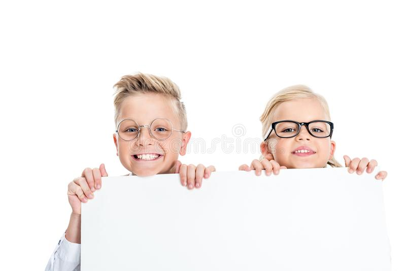 adorable little kids in eyeglasses holding blank banner and smiling at camera royalty free stock photos