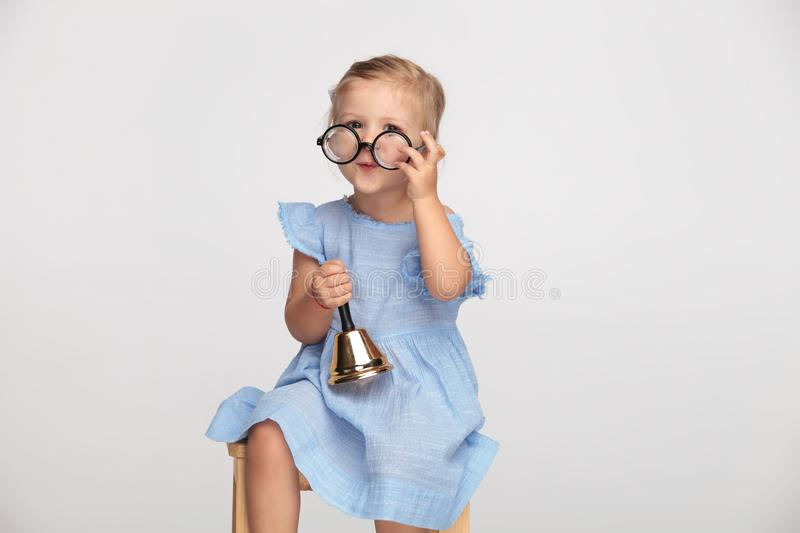 Adorable little girls puts on glasses and rings a bell royalty free stock image