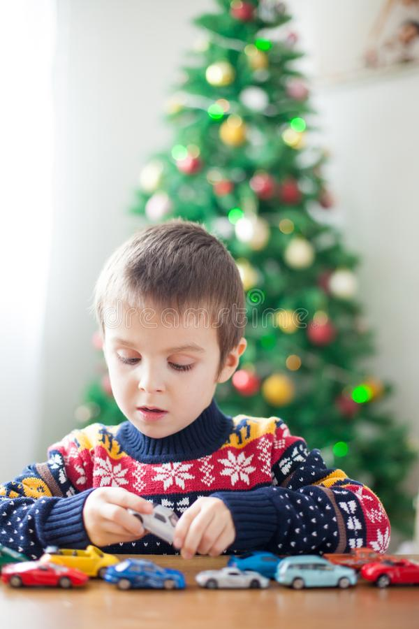 Adorable little preschool boy, playing with toy cars at home on. Christmas, Christmas decoration around him stock photography