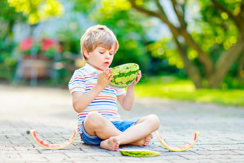 Adorable little preschool kid boy with blond hairs eating watermelon in summer garden. Funny happy child smiling and stock photo