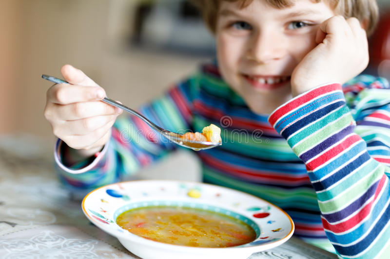Adorable little school boy eating vegetable soup indoor. Blond child in domestic kitchen or in school canteen. Cute kid and healthy food, organic vegan soup stock photos