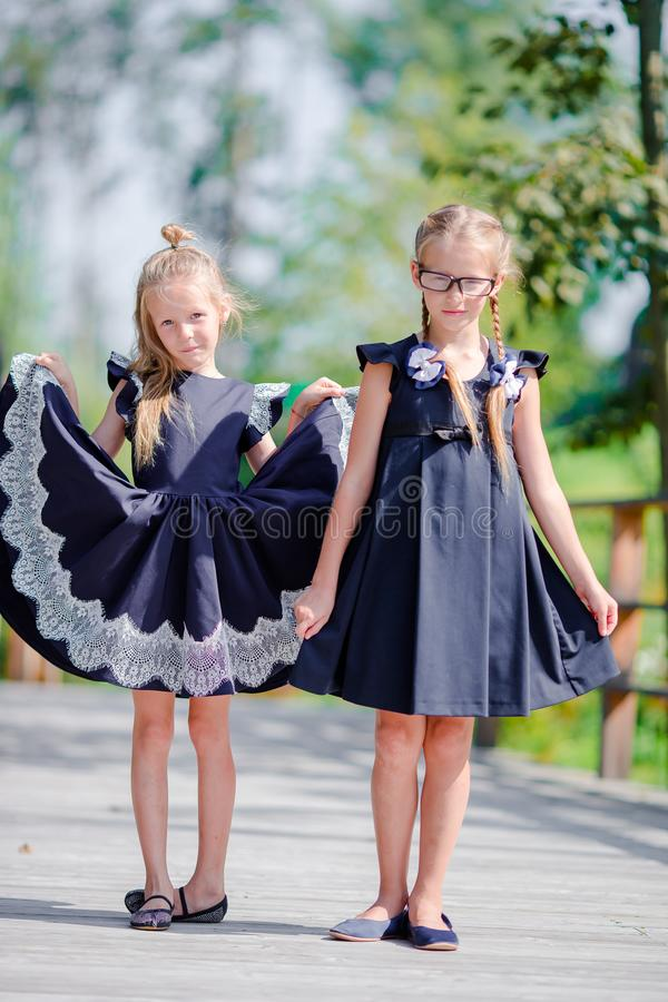 Adorable little school girls outdoors in warm september day. Back to school. Adorable little school girls with notes and pencils outdoor royalty free stock photos