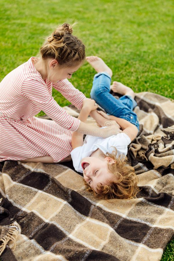 adorable little siblings having fun on plaid on green meadow stock images