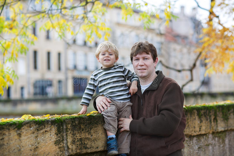 Adorable little son and father in autumn city.
