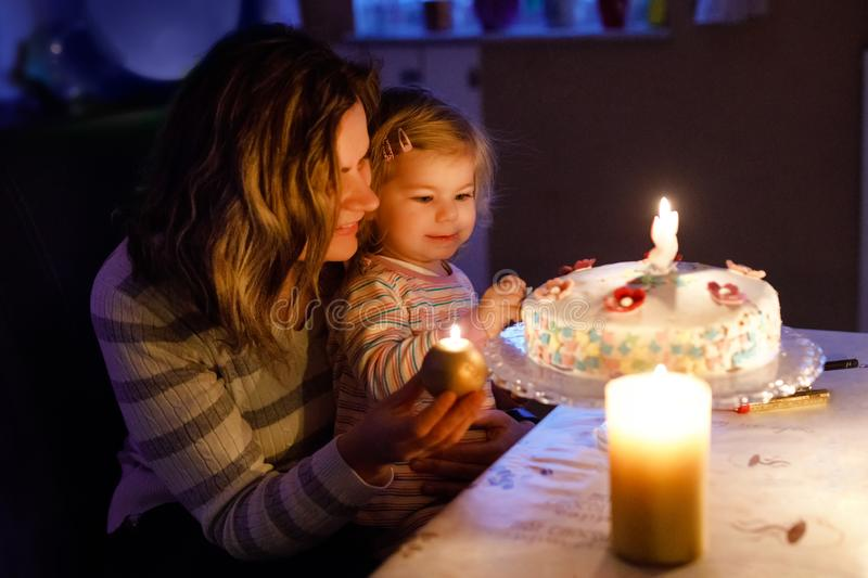 Adorable little toddler girl celebrating second birthday. Baby child daughter and young mother blowing candles on cake. And candles. Happy healthy family stock photo
