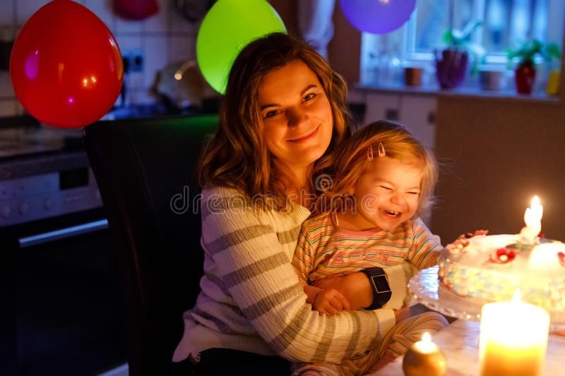 Adorable little toddler girl celebrating second birthday. Baby child daughter and young mother blowing candles on cake. And candles. Happy healthy family stock photos