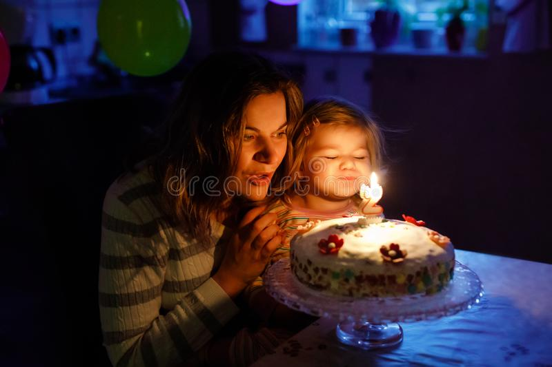 Adorable little toddler girl celebrating second birthday. Baby child daughter and young mother blowing candles on cake. And candles. Happy healthy family stock photography