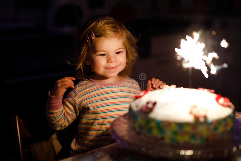 Adorable little toddler girl celebrating second birthday. Baby child eating marshmellows decoration on homemade cake. Indoor. Happy healthy toddler is suprised stock photo